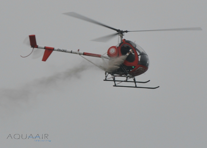asverstrooiing per helikopter door aqua air services